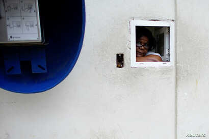 An employee peers from a window at a pharmacy in Havana, Dec. 1, 2017.