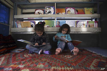 Afghan children read books inside a library on wheels, in Kabul, Afghanistan, March 10, 2018.