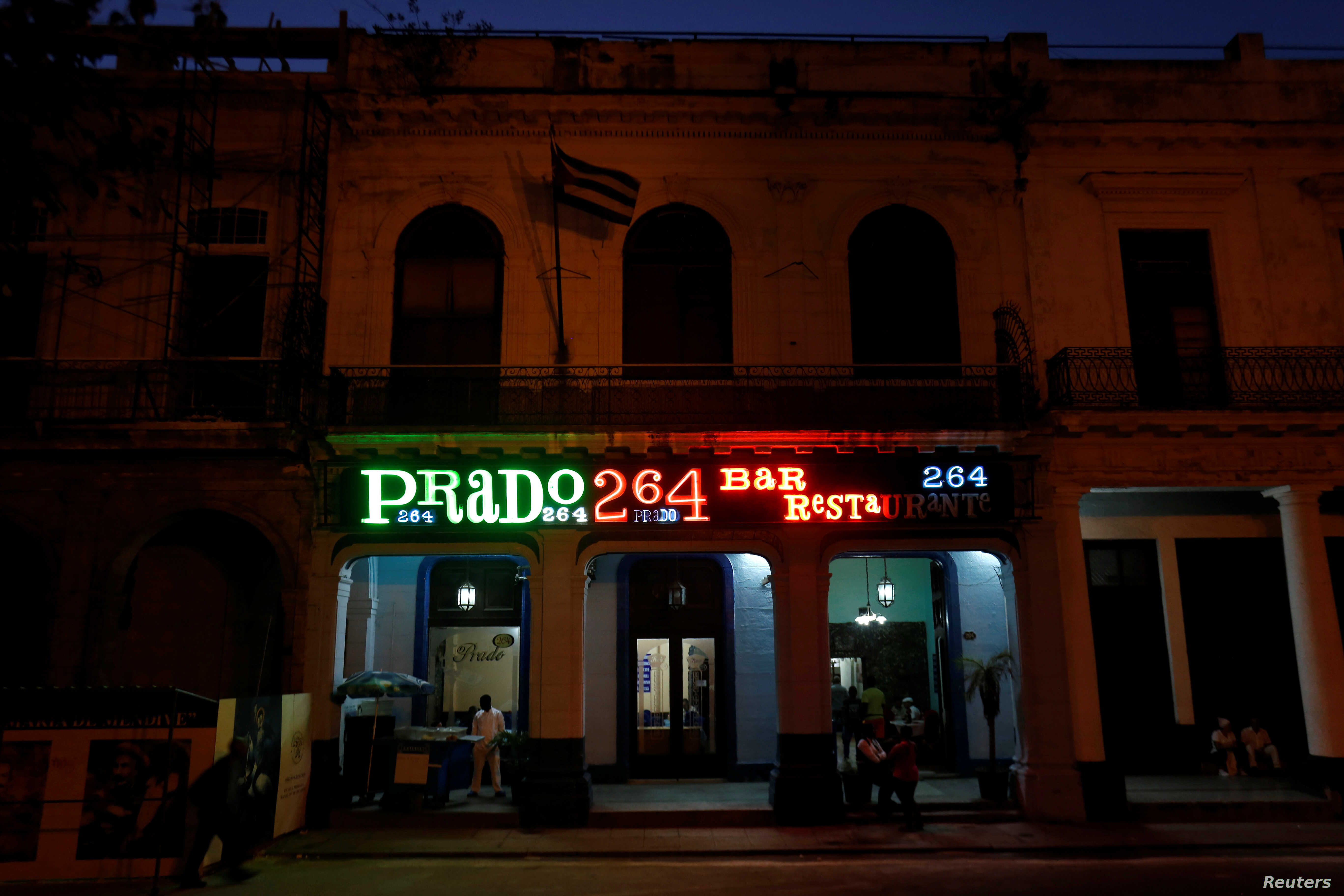 A neon sign shines above the entrance of the restaurant Prado 264, in Havana, Cuba, Feb. 15, 2018.