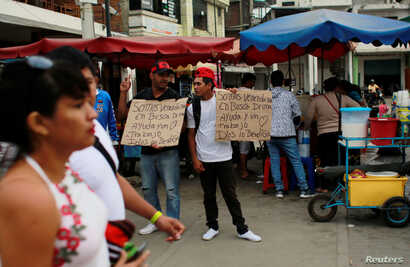 "Venezuelan migrants hold signs that read ""We are Venezuelans looking for help and a job, God bless you"" at the border with Ecuador, in Tumbes, Peru, Aug. 24, 2018."