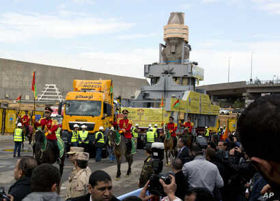 The statue of Egyptian Pharaoh Ramses II is surrounded by honour guards as it is moved to be displayed at a permanent location at the Grand Egyptian Museum (GEM) in Cairo, Egypt, Thursday, Jan. 25, 2018.