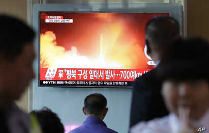 People watch a TV news program showing a file image of a missile launch conducted by North Korea, at the Seoul Railway Station in Seoul, South Korea, May 14, 2017.