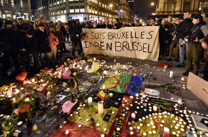 """People hold a banner reading """"I am Brussels"""" behind flowers and candles mourn for the terror attack victims at Place de la Bourse in the center of Brussels, March 22, 2016."""