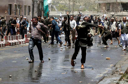 Afghans throw stones towards security forces during a protest in the wake of a deadly bombing Wednesday, in Kabul, Afghanistan, June, 2, 2017.