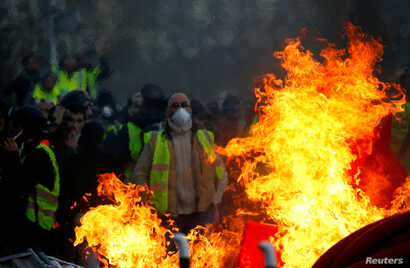 "FILE - Protesters wearing yellow vests are seen behind a fire as they attend a demonstration of the ""yellow vests"" movement in Angers, France, Jan. 19, 2019."