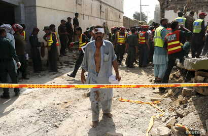 An injured man walks away as rescue workers search after a blast near the home of the home minister of Punjab province, Shuja Khanzada, in Attock, Pakistan, August 16, 2015.