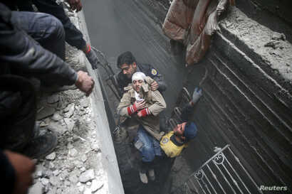 Civil defense help an unconscious woman from a shelter in the besieged town of Douma in eastern Ghouta in Damascus, Syria, Feb. 22, 2018.