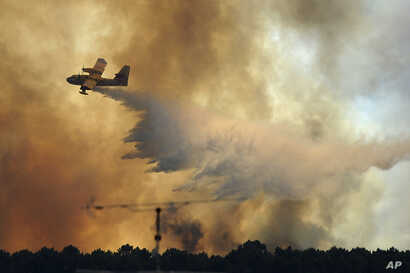A fire fighting aircraft drops water over a fire outside the village of Pedrogao Grande central Portugal, June 19, 2017.