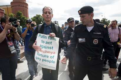 "Russian police detane gay rights activist Peter Tatchell, center, as he holds a banner that reads ""Putin fails to act against Chechnya torture of gay people"" near Red Square in Moscow, Russia, June 14, 2018."