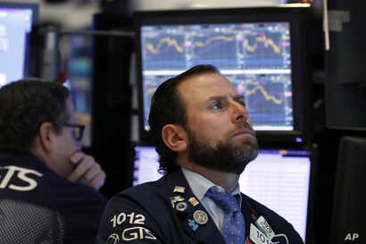 Specialist Michael Pistillo, right, works on the floor of the New York Stock Exchange, Jan. 3, 2019.