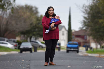 FILE - Blanca Eschbach, 32, poses for a portrait with her daughter Olivia on her first day back at work after a 10-week maternity leave in San Antonio, Texas, March 4, 2019.