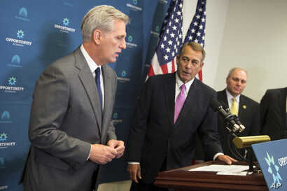 House Majority Leader Kevin McCarthy of Calif., left, accompanied by outgoing House Speaker John Boehner of Ohio, center, and House Majority Whip Steve Scalise of La. speaks during a new conference on Capitol Hill in Washington, Oct. 7, 2015.