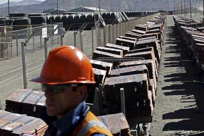 FILE - An operator monitors a train yard where copper cathodes are loaded for shipping to a port, at the Chuquicamata mine and foundry in northern Chile, April 1, 2011.