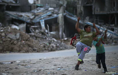 Palestinian children play near houses reportedly damaged during the Israeli offensive, in northern Gaza Strip town of Beit Hanoun, on Oct. 13, 2014.