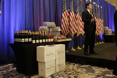 FILE - A secret service agent stands on the stage prior to a scheduled news conference by Republican presidential candidate Donald Trump, Tuesday, March 8, 2016, in Jupiter, Fla. At left  is a display of Trump branded wine, water and steaks.