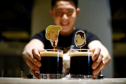 A bartender presents a pair of Donald Trump and Kim Jong Un cocktails called The Bromance at Hopheads Craft Beer Bar and Bistro in Singapore, June 8, 2018.