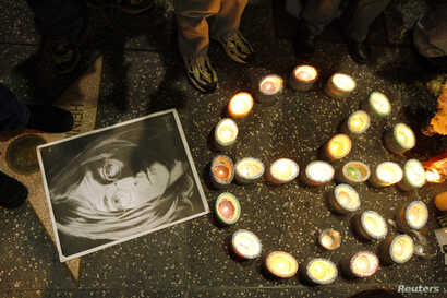 A photo of music icon John Lennon and peace sign made of candles sit on the pavement near Lennon's star during a gathering of fans and supporters in front of the Capitol Records building on the Hollywood Walk of Fame in Hollywood, California December...