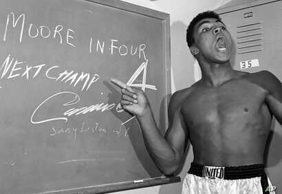 FILE - Young heavyweight boxer Cassius Clay, who later changed his name to Muhammad Ali, points to a sign he wrote on a chalk board in his dressing room before his fight against Archie Moore in Los Angeles, predicting he'd knock Moore out in the four