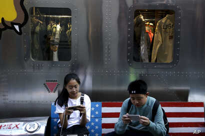 FILE - Shoppers sit on a bench with a decorated with U.S. flag browsing their smartphones outside a fashion boutique selling U.S. brand clothing at the capital city's popular shopping mall in Beijing.