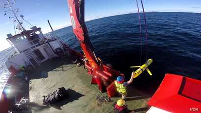 FILE - Crew members aboard the VOS Raasay recover U.S. and British Royal Navy ocean gliders during an exercise off the northwest coast of Scotland, Oct. 8, 2016. U.S. defense officials say a similar unmanned vehicle was seized by the Chinese Navy in ...