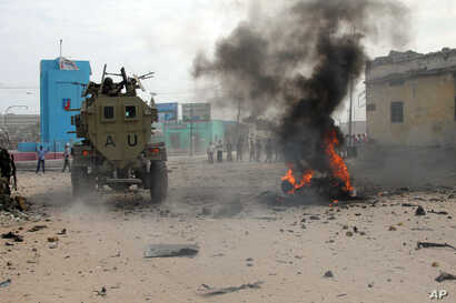 African Union Mission in Somalia (AMISOM) troops ride an amoured vehicle past a burning car in Somalia