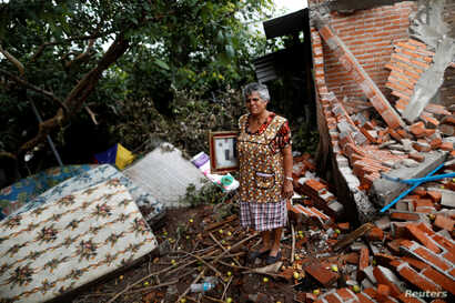 FILE - Maria Guzman, 70, a housewife, stands amid the rubble of her house after an earthquake in San Jose Platanar, at the epicenter zone, Mexico, Sept. 28, 2017.