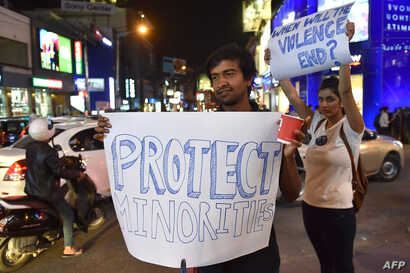 FILE - India students from various colleges hold posters as they stage a candle light vigil in support of the Tanzanian nationals who were recently assaulted by a local mob, in Bangalore on Feb. 4, 2016.
