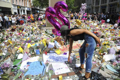 A young woman views of flower tributes  for the victims of Monday's explosion at St Ann's square in central Manchester, England, May 25 2017.
