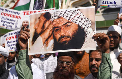 Indian Muslims hold a scratched photo of Jaish-e-Mohammad group chief, Maulana Masood Azhar, as they shout slogans against Pakistan during a protest in Mumbai on February 15, 2019, the day after an attack on a paramilitary Central Reserve Police Forc...