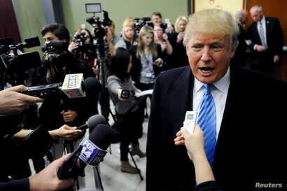 U.S. Republican presidential candidate Donald Trump answers questions from the media ahead of a campaign stop in Spencer, Iowa Dec. 5, 2015.
