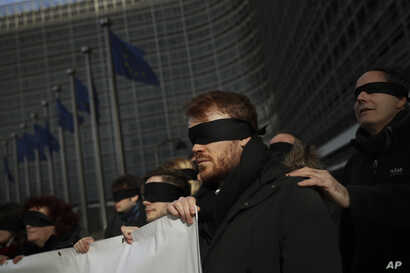 Blindfolded protesters against Brexit hold a banner outside the European Commission headquarters during a meeting between European Commission President Jean-Claude Juncker and British Prime Minister Theresa May in Brussels, Thursday, Feb. 7, 2019.