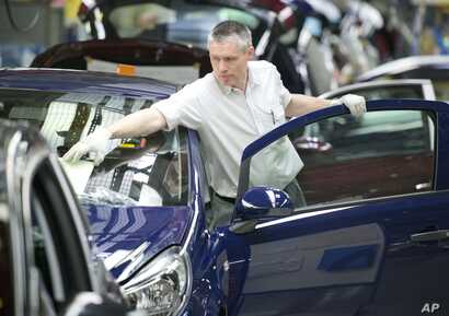 FILE - A worker completes an Opel Corsa car at the German car company Opel Eisenach GmbH, owned by General Motors Corp., in Eisenach, Germany, April 23, 2014.