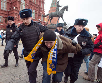 Police officers detain a protester in central Manezhnaya Square in Moscow,  on March 2, 2014, during an unsanctioned rally against the Russia's military actions in Crimea. Police arrested today hundreds in Moscow and dozens in St.Petersburg  as they