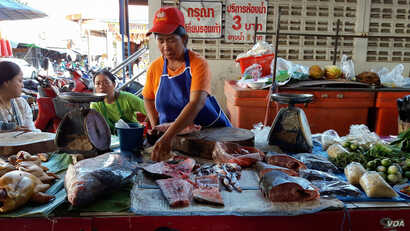 A fish seller at a local market in Chiang Khan town, Thailand sees cutting out the fresh fish Mekong River on July 25, 2016. (Neou Vannarin/VOA Khmer)