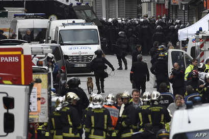 Firefighters and policemen are gathered in the northern Paris suburb of Saint-Denis city center, on November 18, 2015, as French Police special forces raid an appartment, hunting those behind the attacks that claimed 129 lives in the French capital f...