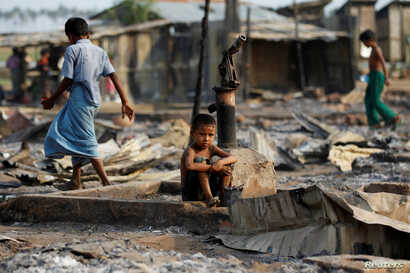 FILE - A boy sits in a burned area after fire destroyed shelters at a camp for internally displaced Rohingya Muslims in western Rakhine State near Sittwe, Myanmar, May 3, 2016.