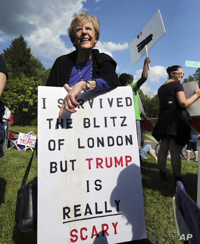 FILE - Enid Pensack, of Pennington, N.J., holds a sign as she stands with others outside an event where Republican presidential candidate, Donald Trump and New Jersey Gov. Chris Christie were to appear on May 19, 2016 in Lawrenceville, N.J.