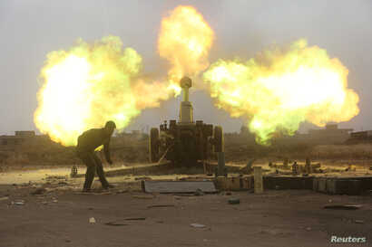 Popular Mobilization Forces fire toward Islamic State militants during a battle on the outskirts of Al-Ba'aj, west of Mosul, Iraq, May 26, 2017.