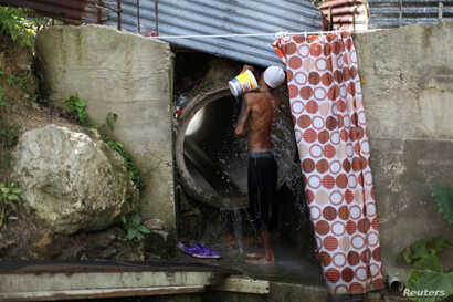Israel Ayala takes a bath with water coming through a pipe, after the island was hit by Hurricane Maria in September, in Toa Alta, Puerto Rico, Oct. 19, 2017.