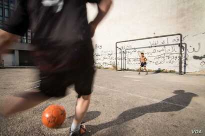 Youngsters play football on the streets of Beirut.