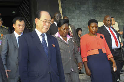 FILE - North Korea's ceremonial leader, Kim Yong Nam, foreground,left, the head of North Korea's parliament, is escorted into Uganda's parliament by its Speaker Rebecca Kadaga, center, Commissioner Rosemary Seninde, center-right, and Uganda's For...