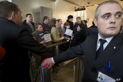 """Hard-currency mortgage holders, show banners reading """"Hard-Currency Mortgage is Plague"""", as they gather during a protest in a bank office in Moscow, Russia, Jan. 28, 2016."""