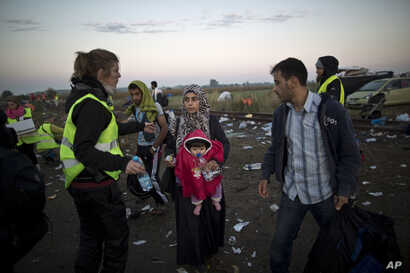 A volunteer, left, hands water and food to a Syrian refugee woman carrying a baby after she crossed the border between Serbia and Hungary in Roszke, southern Hungary, Sept. 14, 2015.