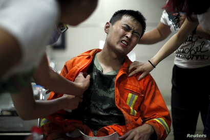 A firefighter reacts as he receives treatment at a hospital after the explosions at the Binhai new district in Tianjin, China, Aug. 13, 2015.