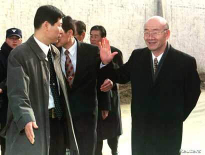 FILE - Former South Korean president Chun Doo-hwan, right, waves goodbye as he is escorted by a secret service agent outside the walls of Anyang Prison to a waiting car shortly after being released from the jail on a special pardon in Anyang, Dec. 22...