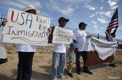 FILE - Mexican border residents and members of the Border Network for Human Rights (BNHR) hold up placards and a banner during a protest to reject border militarization and the deportation of children, outside a detention center in El Paso, Texas, Au...