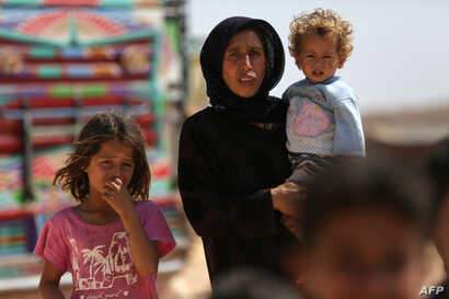 FILE - A woman who fled her village in Syria's Idlib province carries a child at a camp in Kafr Lusin near the border with Turkey,  September 9, 2018.
