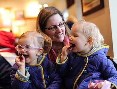 FILE - Michelle Moore poses for a photo with her twin daughters, Sierra (right)  and Savannah in Lake Oswego, Oregon. Moore is among the vaccine skeptics who have been widely ridiculed since more than 100 people fell ill in a measles outbreak traced ...