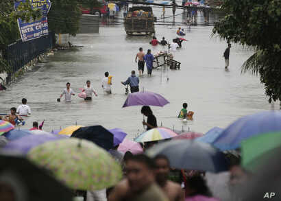 Residents wade along flooded roads in Quezon City, north of Manila, Philippines, August 7, 2012.