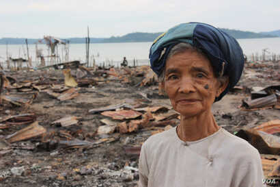 A woman stands in front of a burned out Muslim neighborhoud, Kyauk Phyu, Rakhine State, Burma, November, 2012. (D. Schearf/VOA)